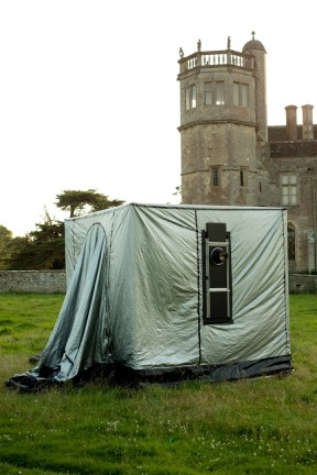 Color photograph of a cube-shaped tent with protruding camera lens before a stone manor house