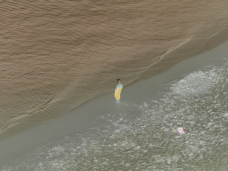 Inverted color photograph from above of a person standing on the edge of the seashore looking at the water