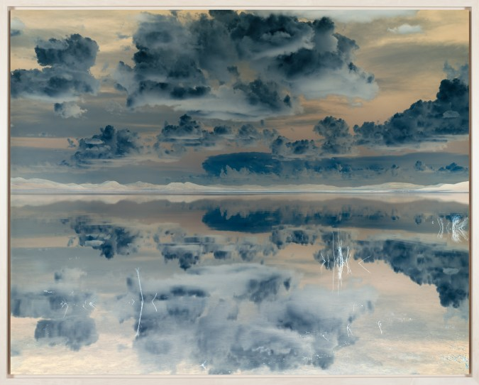 Inverted color photograph of a still body of water reflecting a cloudy sky above