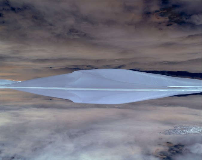 Inverted color photograph of a sand dune reflected in a still body of water