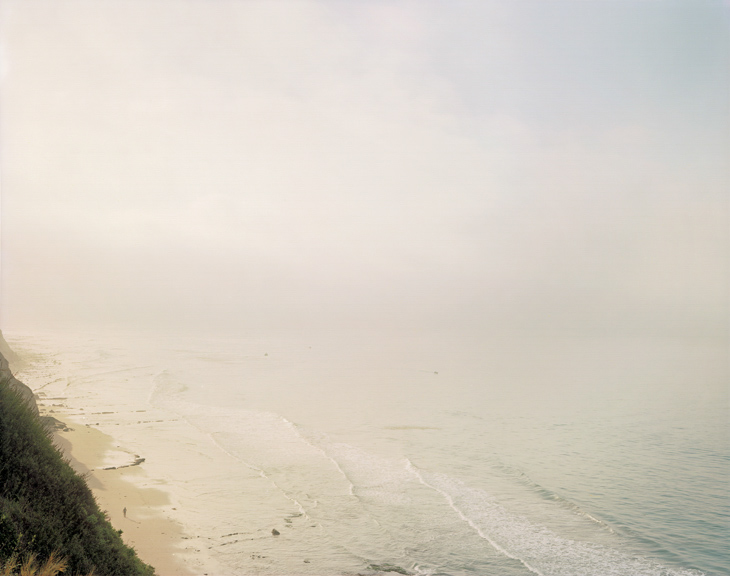 Color photograph of a lone figure walking along a beach shrouded in mist
