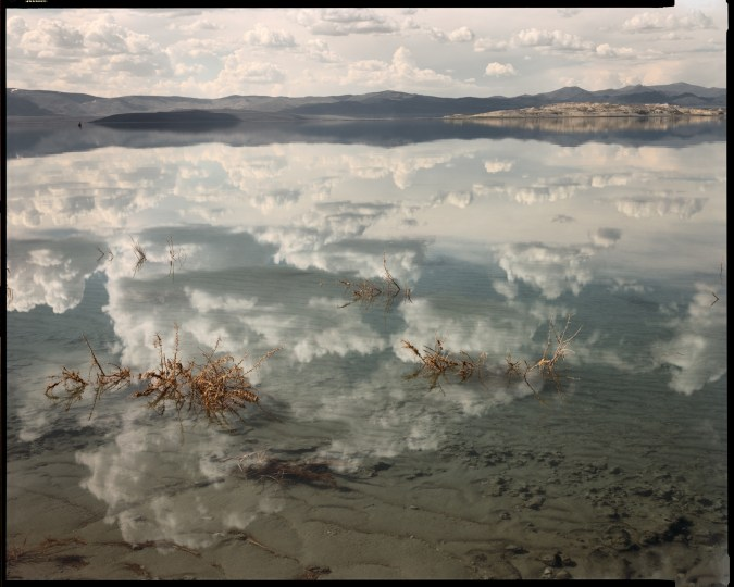 Color photograph of a still lake reflecting a cloudy sky and low mountains on the horizon