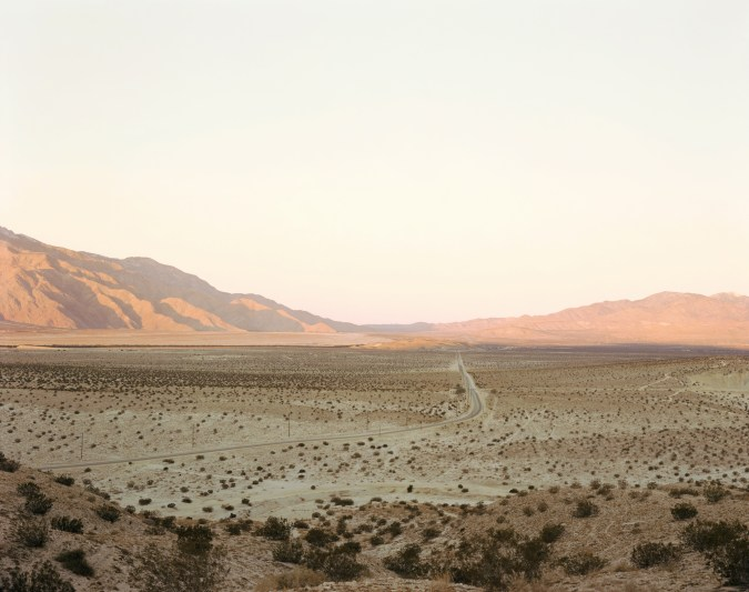 Color photograph of a road through a desert valley with mountains on the horizon