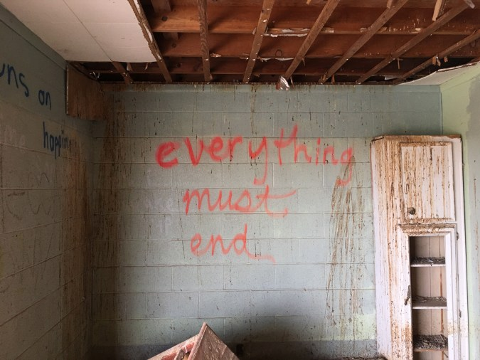 Color photograph of a destroyed interior with grafitti on the walls.