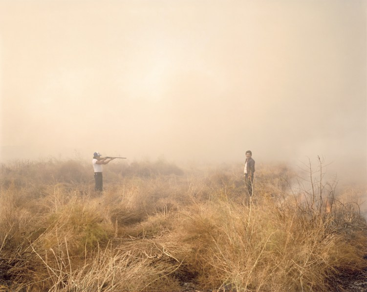 Color photograph of a man pointing a rifle at another man, both standing in a smokey scrubland