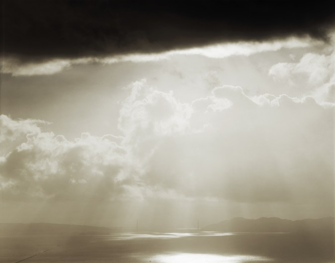 Color photograph of the distant Golden Gate Bridge under beams of sunlight breaking through a cloudy sky