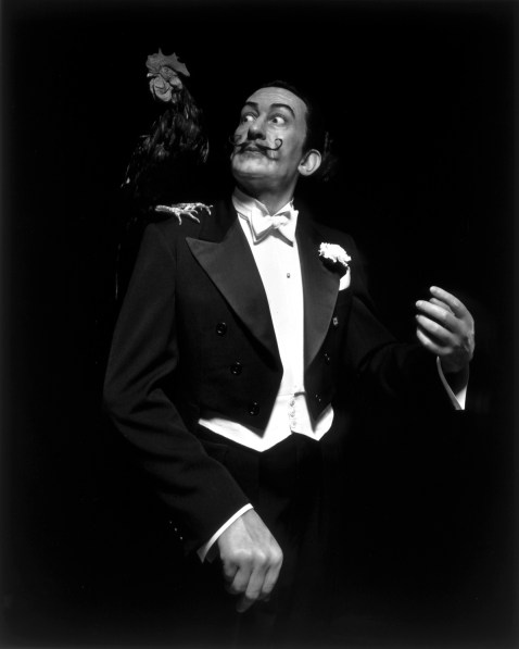 Black-and-white frontal portrait of a wax figure of a mustached man in a white-tie tuxedo looking in surprise at a rooster on his shoulder