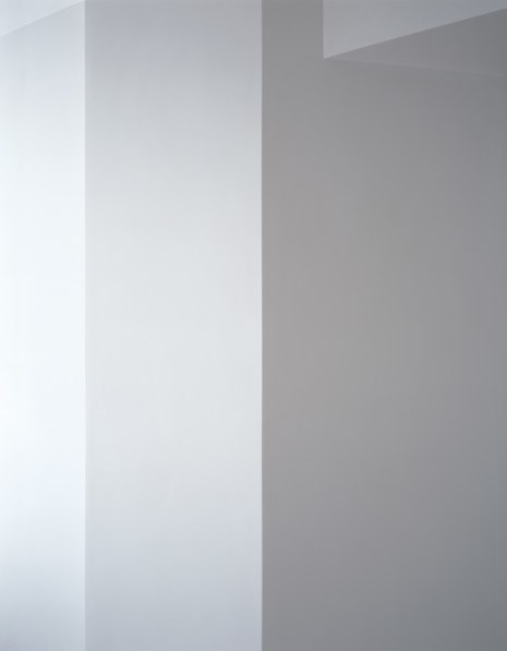 Photograph of a white wall with ceiling beam in varying shades of light gray