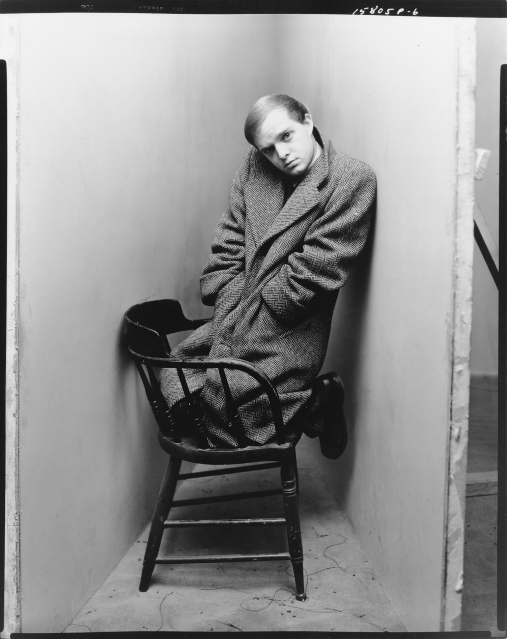 Black-and-white photograph of a man in a long coat kneeling on a wooden chair