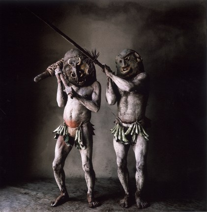 Color photographic studio portrait of two men in oversized masks wielding a club and a sword