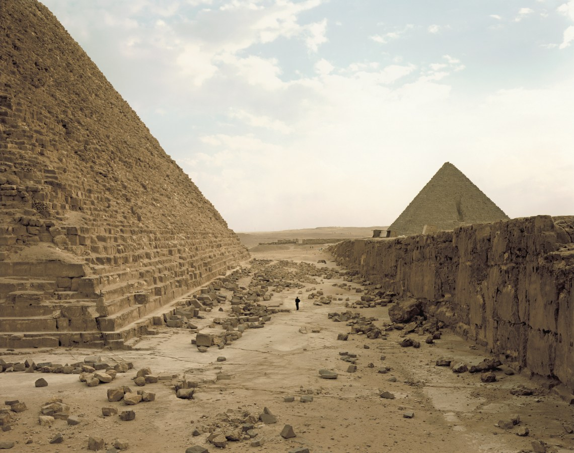 Color photograph of a lone figure looking up at a pyramid