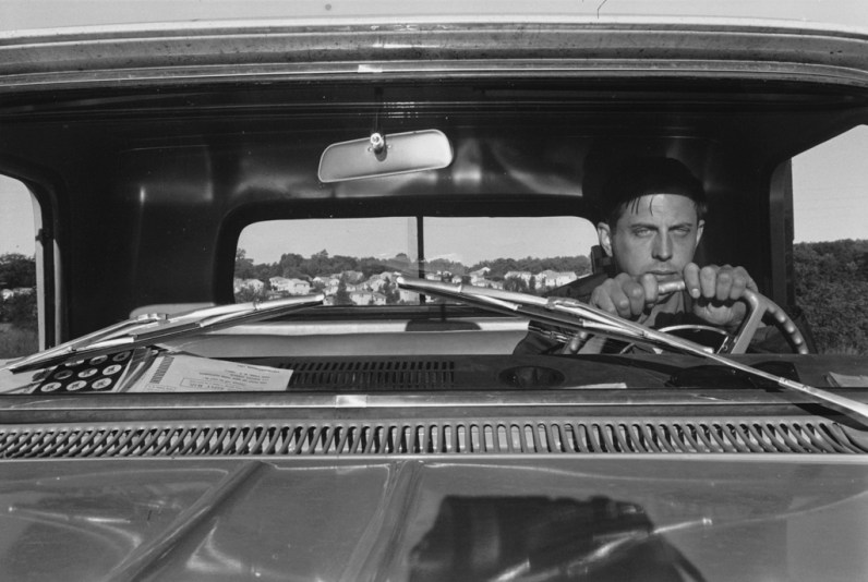A black and white photograph of a self portrait of the artist at the wheel of a pickup truck