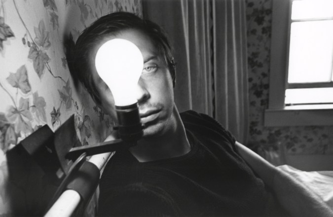 A black and white photograph of a self portrait of the artist with an illuminated lightbulb in front of his face