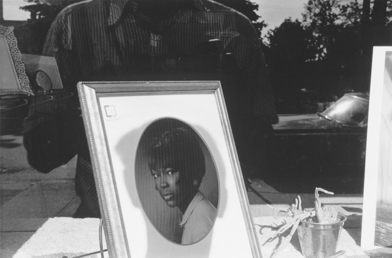 A black and white photograph of the artists shadow on a framed portrait of a woman