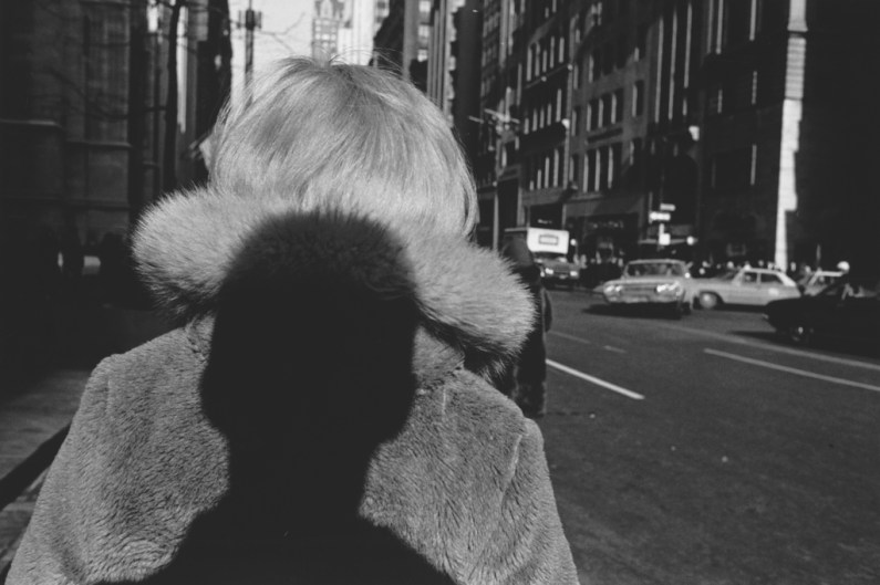 A black and white photograph of the artists shadow on a woman's back in a city street