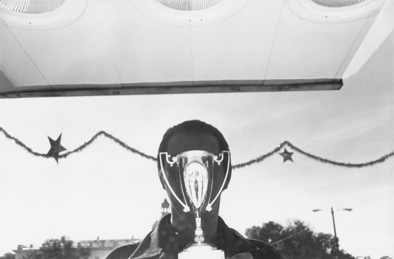 A black and white photograph of the reflection of the artist over a shining trophy in a store window