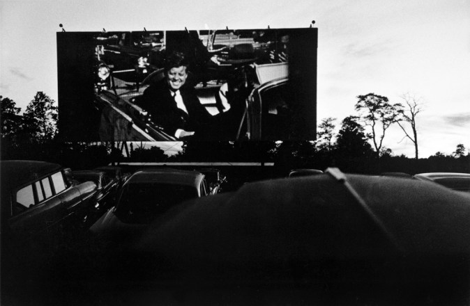 Black-and-white photograph of JFK on screen at a drive in theater