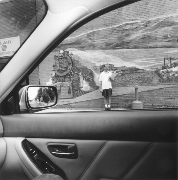 Black and white photo looking out the window of a car at a person standing in front of a mural