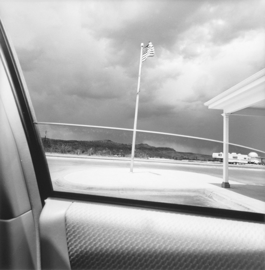 Black and white photograph out the window of a car of a flag pole with American Flag and overcast sky