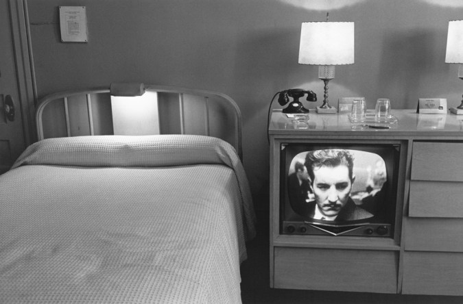 Black-and-white photograph of a neatly made bed and a television with a mans face on screen