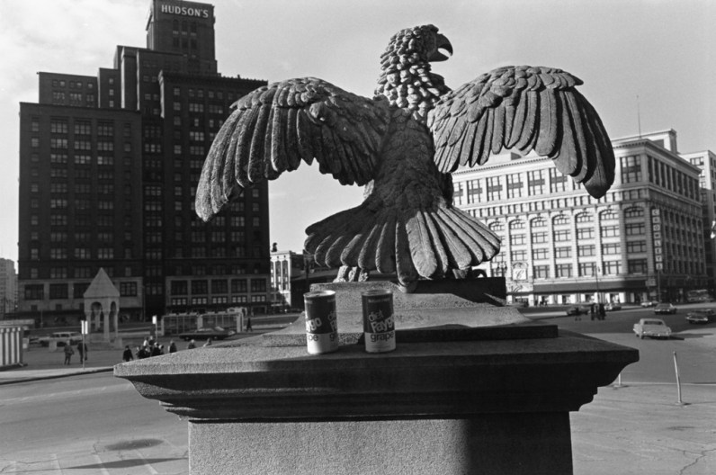 Black and white photograph of an eagle monument with buildings in the background