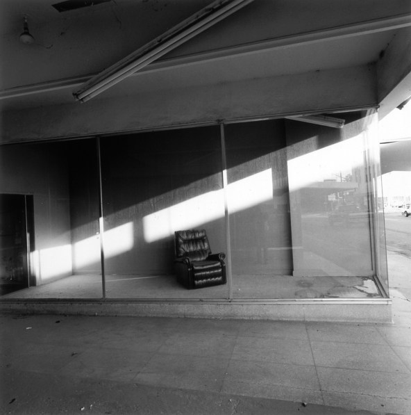 A black and white photograph of a single recliner in an empty store front display