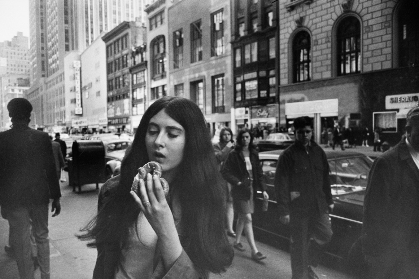 Black-and-white photograph of a woman on a city sidewalk holding a pretzel to her mouth