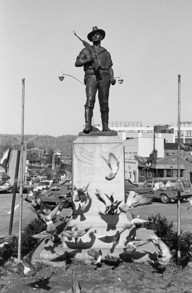 Black and white photograph of a monument surrounded by pigeons