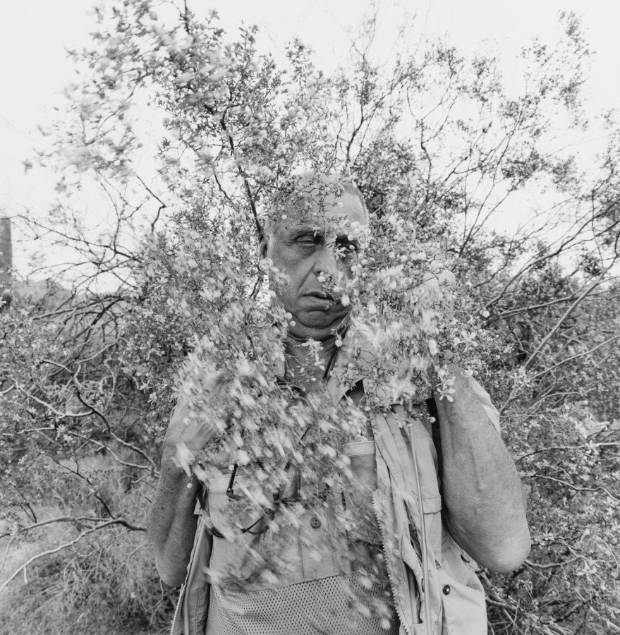 A black and white photograph of a self portrait of the artist standing behind a tree branch