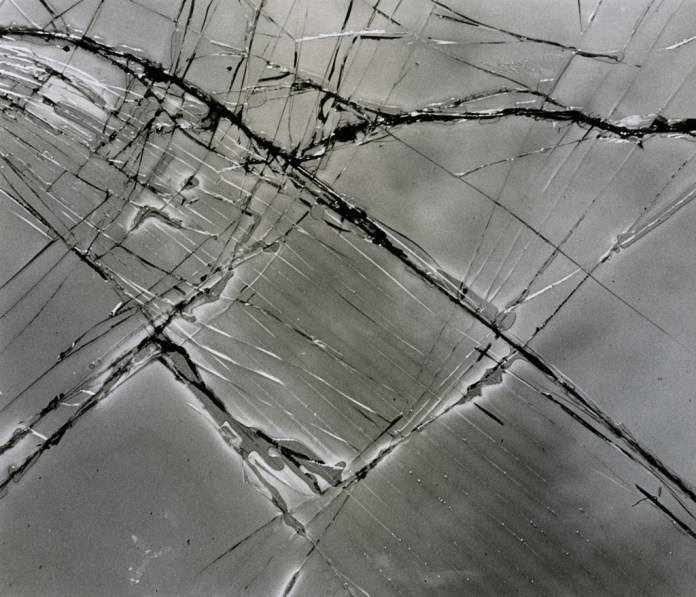 Black-and-white photograph of a cracked and scratched glass surface with linear fractures