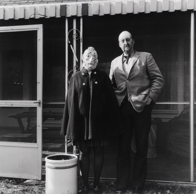 Black-and-white photograph of two people in rubber masks standing in front of a screened-in terrace