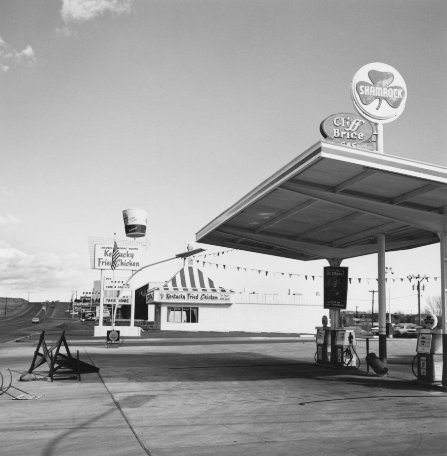 A black and white photograph of an empty gas station with a Kentucky Fried Chicken restaurant in the back ground.