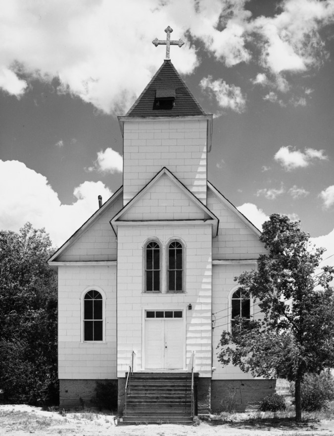 A vertical black and white photograph of an old wooden church with trees at each side and a cloudy sky.