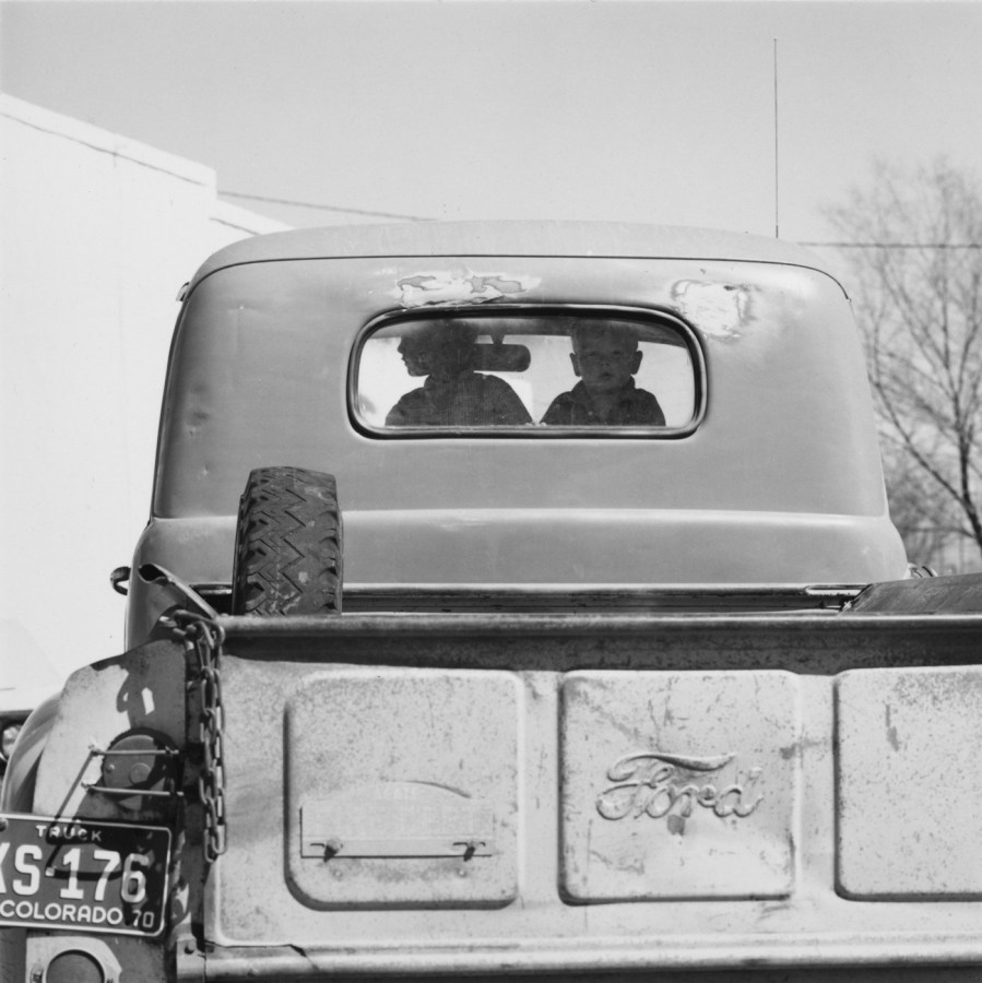 A black and white photograph of two children looking out the rear window of a beat up early 1950's Ford pick up truck.