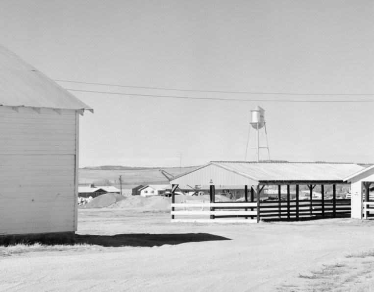 A black and white photograph of empty fairgrounds with a water tank in the distance and a brightly lit clear sky.