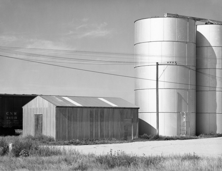 A black and white photograph of a train car, a windowless structure, and silos against a brightly lit sky and telephone wires.