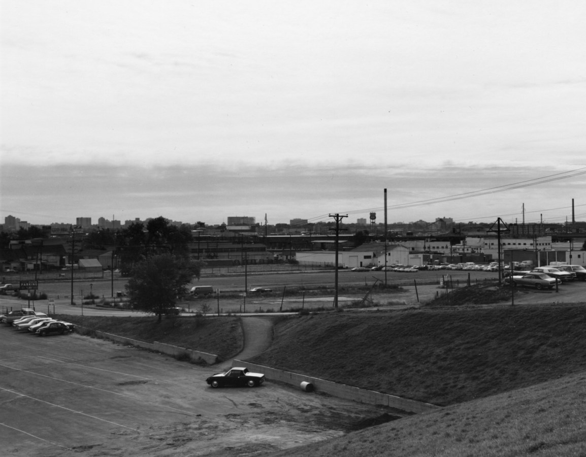 A black and white photograph of an industrial area with parking lots and cars.