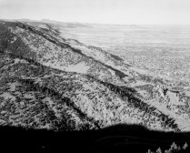 A black and white photograph of expansive mountains with trees and a hazy horizon.
