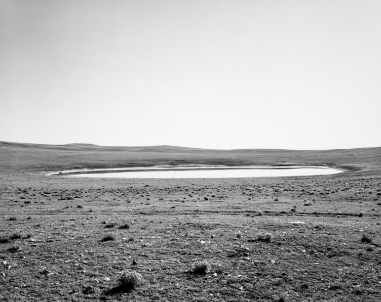 A black and white photograph of a small lake and a clear sky.