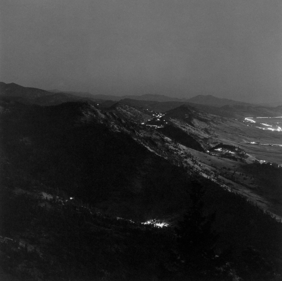 Black-and-white photograph of distant town lights and mountains at night