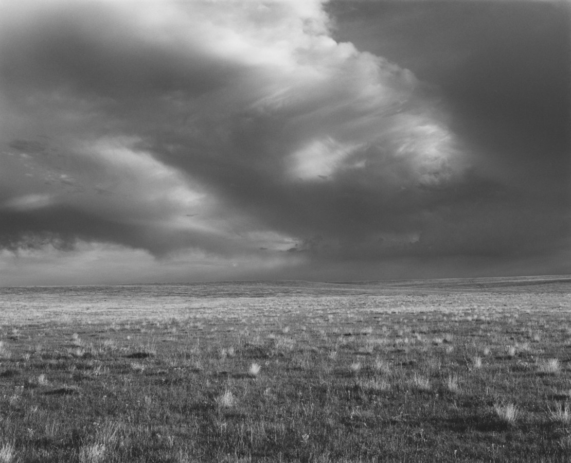 A black and white photograph of an open grassy field with storm clouds in the sky.