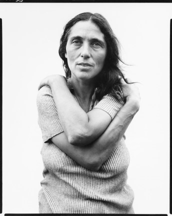 black-and-white photograph of a woman with her arms wrapped around herself against a white background
