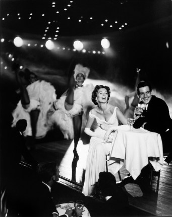 black-and-white photograph of a man and woman at a table on stage with dancers in the background