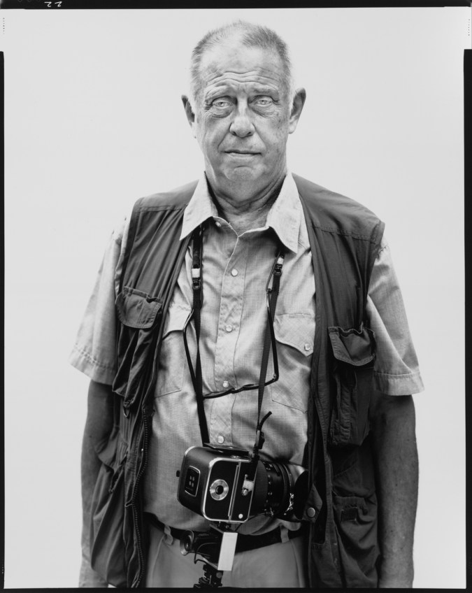 black-and-white photograph of a man wearing a vest with a camera around his neck against a white background