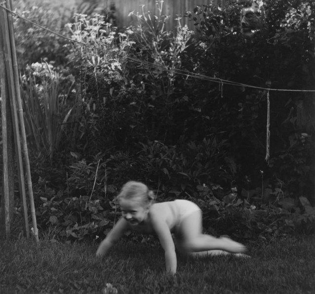 Black-and-white photograph of a young girl crawling through grass in a garden