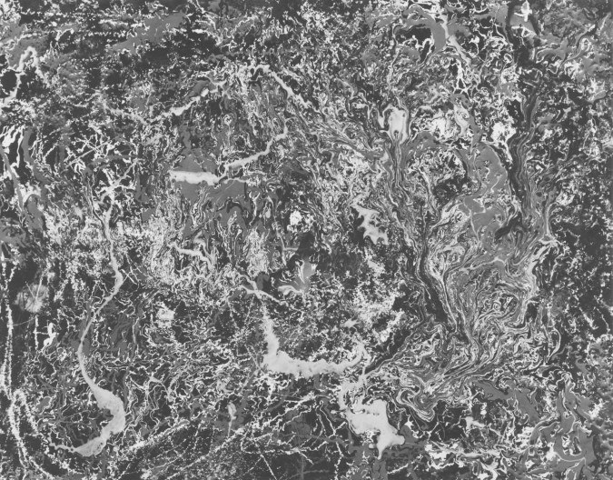 Black-and-white photograph of a foaming, marble-textured liquid surface