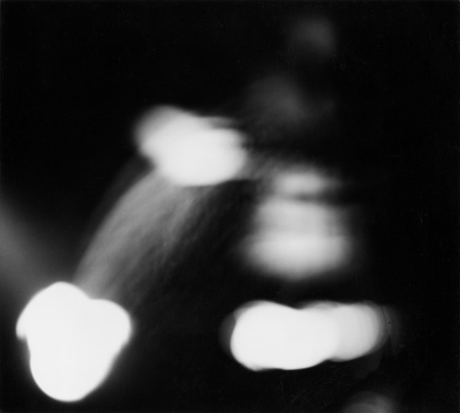 Black-and-white out-of-focus photograph of three blobs of light in a triangular arrangement