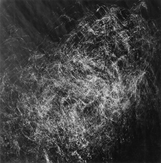 Square black-and-white photograph of light and shadow filtering through rippling water
