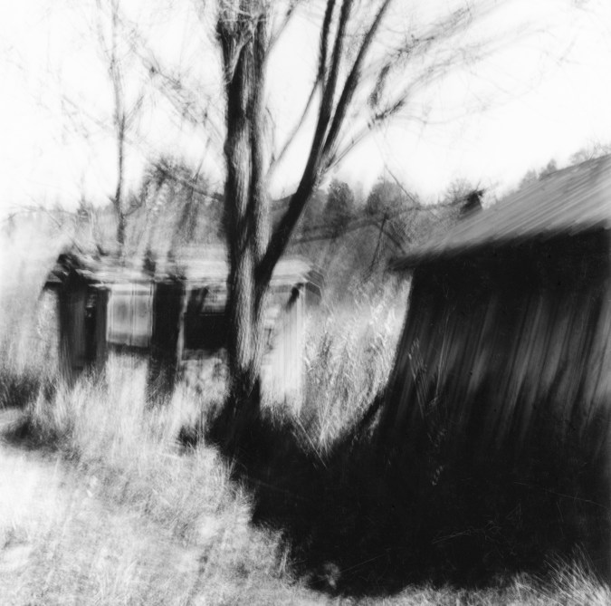 Black-and-white multiple-exposure photograph of a bare tree between two collapsing wooden sheds