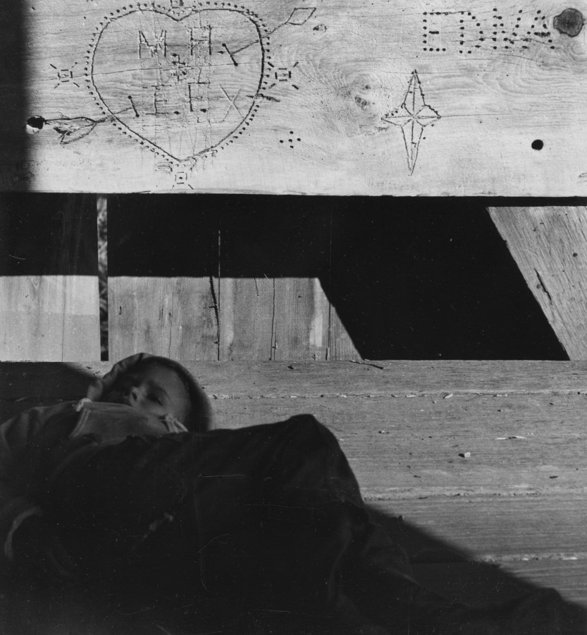 Black-and-white photograph of a child lying under a graffitied wooden panel with carved initials and drawings